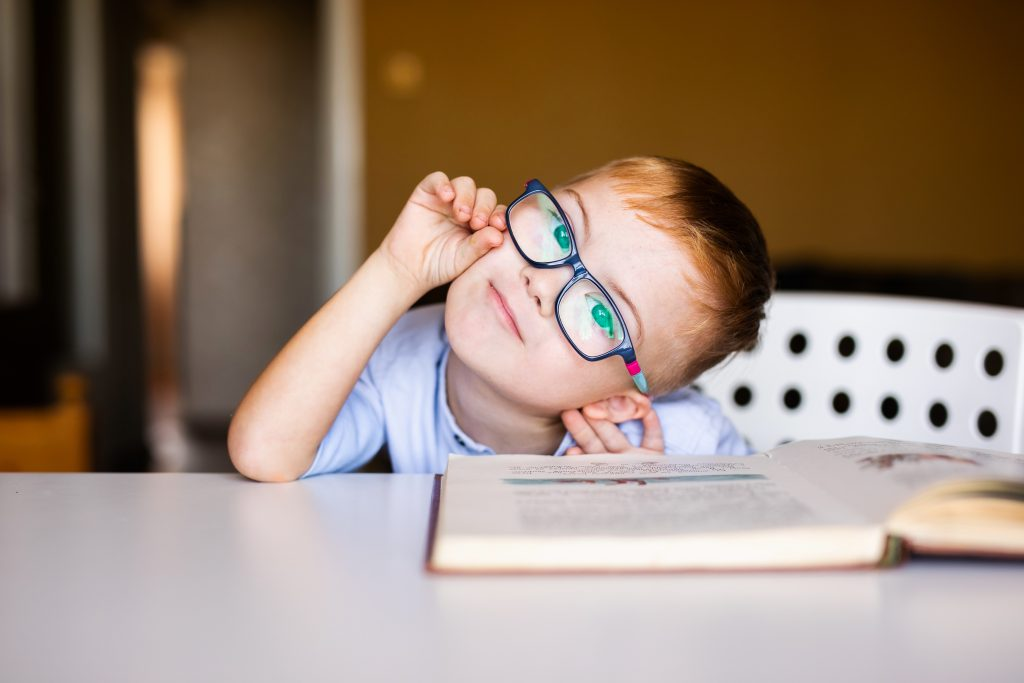 Cute toddler boy with down syndrome with big glasses reading interesting book.